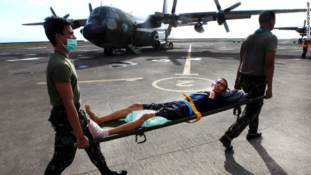 Philippine military personnel carry an injured survivor to an evacuation flight at the Tacloban airport November