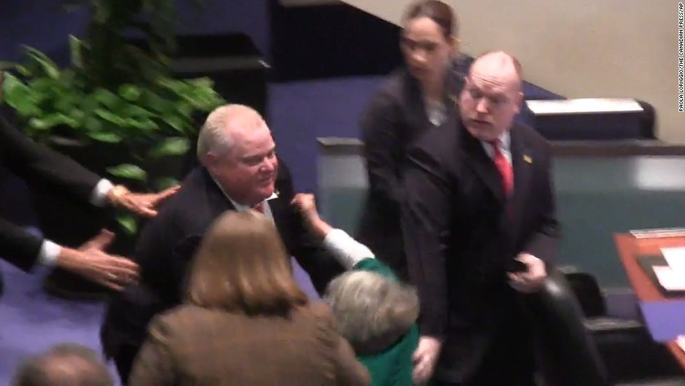 Toronto Mayor Rob Ford accidentally knocks down Councillor Pam McConnell, in green, as he runs toward hecklers in the audience at City Hall in Toronto, on Monday, November 18. Toronto's City Council voted Friday to strip Ford of his ability to govern in case of an emergency and to appoint and dismiss his senior staff, unprecedented moves aimed at reining him in.