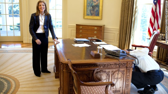 President Barack Obama examines his Oval Office desk while visiting with Kennedy in 2009. Obama was recalling the <a href='http://www.whitehousemuseum.org/furnishings/resolute-desk.htm' target='_blank'>famous photograph</a> of Kennedy's brother peeking through the desk.