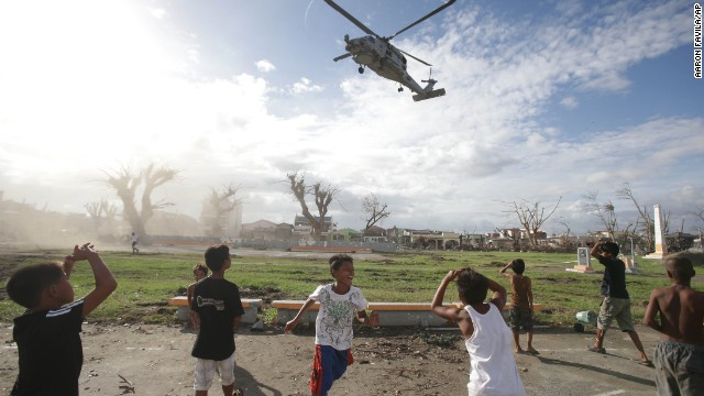 Typhoon survivors watch as a U.S. helicopter lands to deliver relief goods in Tanauan, Philippines, on Wednesday, November 20.