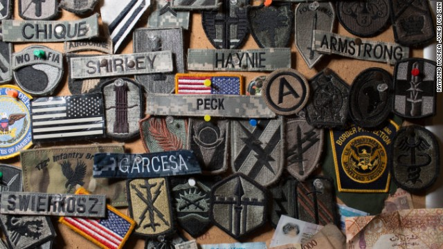 A corkboard full of military patches and souvenirs is mounted to the wall of a Starbucks near a security checkpoint. Employees say troops who come through the airport offer the patches as a way of saying thanks, since the coffee shop won't let them pay.