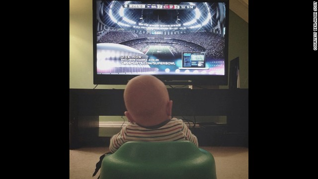 Ward watches football with his dad from the comfort of their living room.