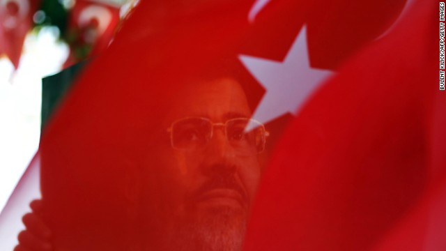 A portrait of ousted Egyptian president Mohamed Morsy is seen through a Turkish flag during a rally in Istanbul.
