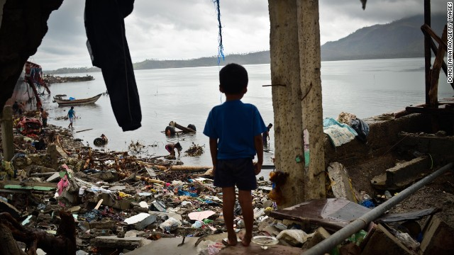A boy peers out of a damaged structure near the shoreline on November 23, 2013 in Tacloban, Philippines.