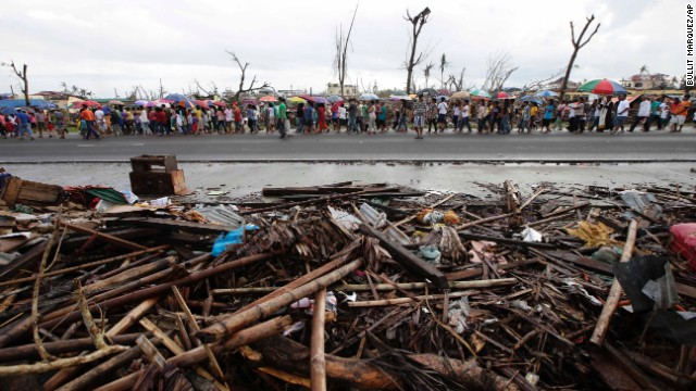 Typhoon survivors walk down a road in Palo, Philppines, during a procession for typhoon victims on November 24.