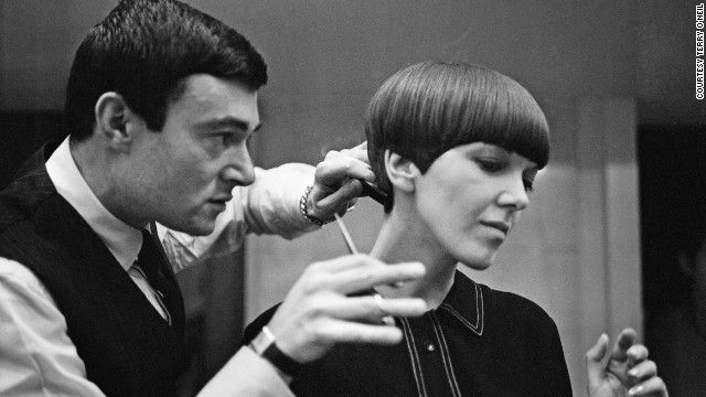 "Legendary hairdresser Vidal Sassoon applies the finishing touches of his trademark ""wedge bob cut"" to miniskirt inventor Mary Quant. ""I was walking down Bond Street and there was a picture of a haircut that knocked me sideways. I knew I wanted <i>my </i>hair cut like <i>that,"" </i>says Quant."