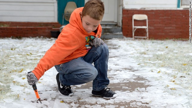Phillip Miller, 8, uses a hammer to break up the ice on the walkway in front of his family's home in Odessa, Texas, on November 24.