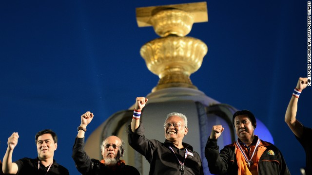 Thai opposition leaders Suthep Thaugsuban, center, and former Prime Minister Abhisit Vejjajiva, left, clinch their fists as they appear on stage during a rally at Democracy Monument in Bangkok Sunday.