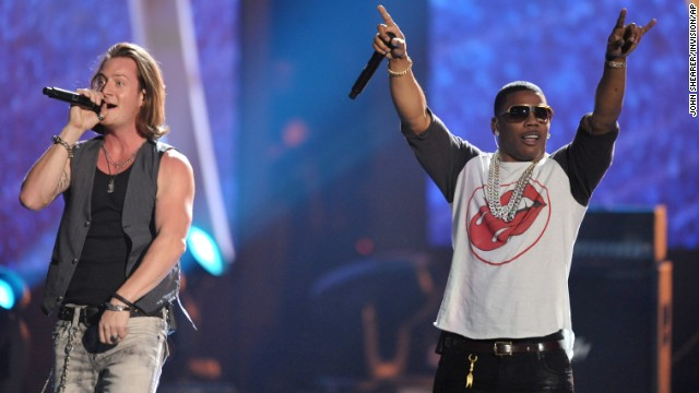 Tyler Hubbard, left, of the musical group Florida Georgia Line performs on stage with rapper Nelly.