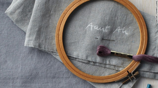 1. Handwrite name on a small piece of paper. Put transfer paper on a napkin and name paper on top, then trace name with pen. 2. Place napkin in embroidery hoop. Embroider name with stem stitch: Bring needle through to right side of napkin, then insert back through at a slight diagonal, about 1/4 inch to right. Bring needle back up 1/8 inch to left, just above halfway point of first stitch. Continue stitching at slight diagonal, making all visible stitches the same length. Repeat for all napkins. (For more instructions, go to <a href='http://marthastewart.com/embroidery-how-to' target='_blank'>marthastewart.com/embroidery-how-to</a>.)