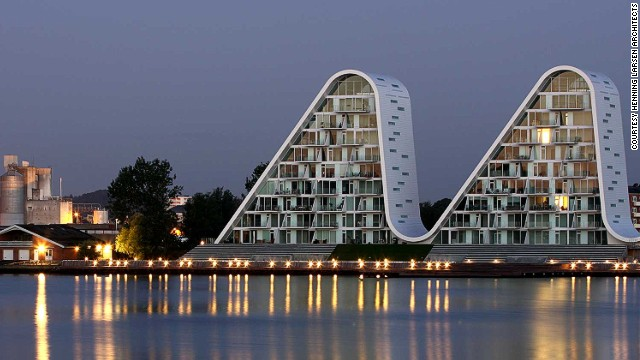 The Wave building in the Danish town of Vejle mirrors the soft movements on the surface of the fjord during the day, and resembles illuminated mountain peaks at night.