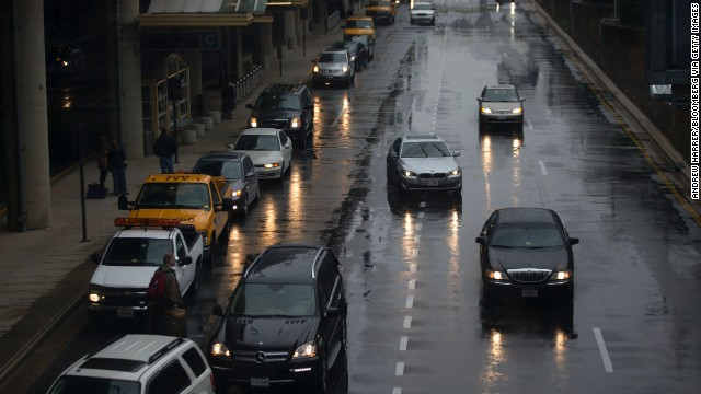 Vehicles pick up passengers in heavy rain at Reagan National Airport on Novemb