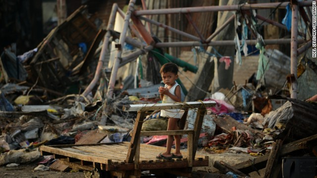 A child stands on a wooden cart among destroyed houses in Tacloban on Tuesday, November 26.