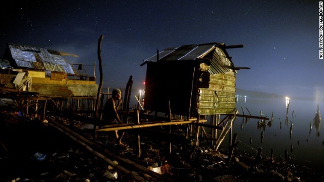A man rests on his damaged house along the shore in Tacloban on Monday, November 25.