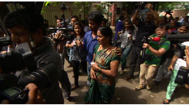 Nirbhaya's mother and brother walk through a media swarm.