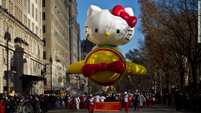 Spectators watch the Hello Kitty balloon float by.