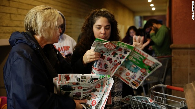Katie Stroh and Gretchen Burkhardt check out sale flyers while waiting outside a Kmart store November 28 in Anaheim, California.