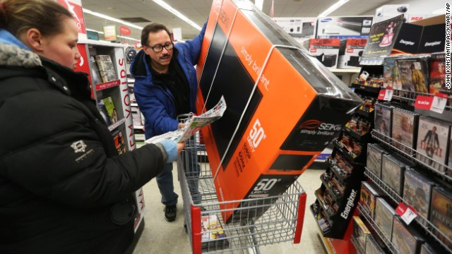 Luis Torres and his daughter Stephanie search for more deals after picking up a 50-inch television at a Chicago Kmart on November 28.