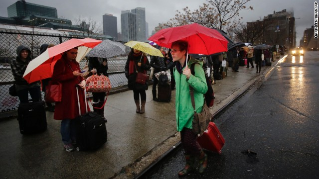 Passengers wait for a BoltBus to arrive during a light rain on Wednesday, November 27, in New York. A wall of storms packing ice, sleet and rain threatened to suspend holiday travel plans as millions of Americans took to the roads, skies and rails.