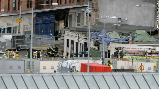 Rescue workers attend the scene Saturday at a pub in Glasgow where a police helicopter crashed.