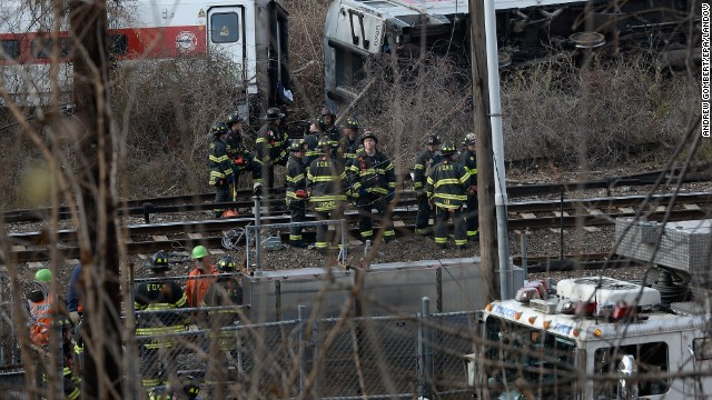 Firefighters and rescue personnel work at the scene of the passenger train derailment near the Spuyten Duyvil station.