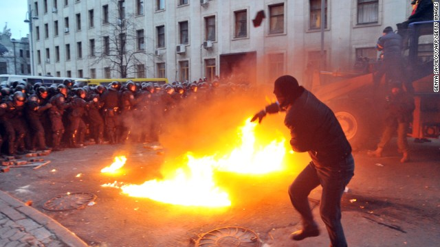 "A protester throws stones toward riot police on December 1. The crowd chanted ""Revolution"" and ""Down with the Gang"" as it gathered in Independence Square."