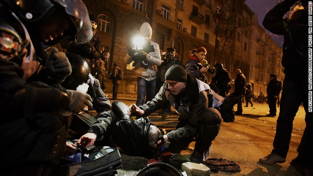 Police and protesters look at an injured person near the presidential office on December 1.