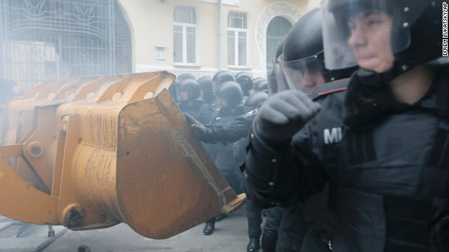 Protesters use a bulldozer during clashes with police at the presidential office in Kiev on December 1.