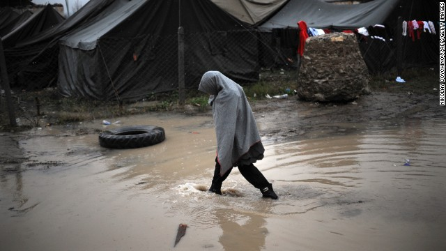 A girl crosses a puddle during the first snowfall of the season in a refugee camp set in Harmanli, Bulgaria, on Wednesday, November 27.