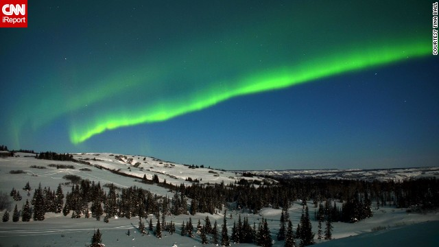 "The lights of the aurora borealis shine bright in this 2012 photo by Tina Ball, who stayed out in the snow for almost four hours ""watching the sky dance."""