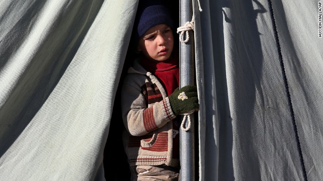 A Syrian child looks out from his tent at a refugee camp in the border town of Arsal, Lebanon, on Friday, November 29.
