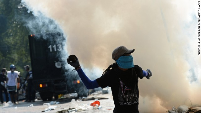 A protester throws a stone at police Monday, December 2, during a rally outside government headquarters in Bangkok, Thailand.
