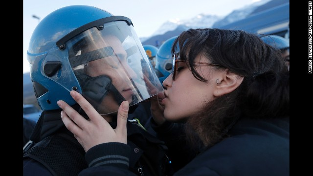 <strong>November 16:</strong> A woman kisses a police officer during a protest of a high-speed train line in Susa, Iran.