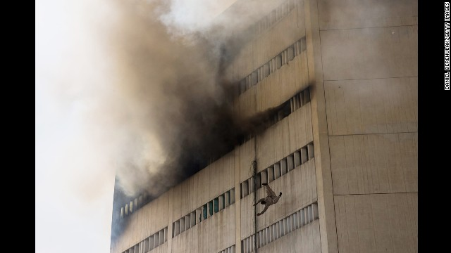 <strong>May 9:</strong> A man overcome by fumes falls out of a window as a fire burns at the Lahore Development Authority Plaza in Lahore, Pakistan.