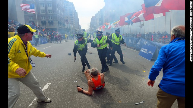 <strong>April 15:</strong> Police officers stand over marathon runner Bill Iffrig as a second explosion sounds near the finish line of the Boston Marathon. Three people were killed and at least 264 were injured in the terror attack.