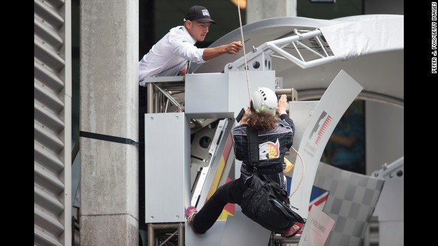 <strong>August 25:</strong> A man threatens to cut the rope of a Greenpeace protester at the Belgian Grand Prix in Spa, Belgium.