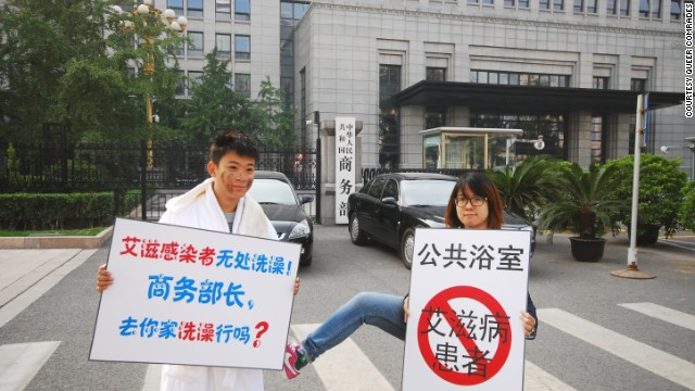 Activist Liu Shi, left, stages a protest after a proposal to ban HIV/AIDS sufferers from entering bathhouses. His sign reads: