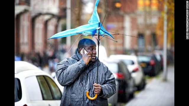 <strong>December 5:</strong> A man holds a broken umbrella in Utrecht, Netherlands, as heavy storms move across northwestern Europe.