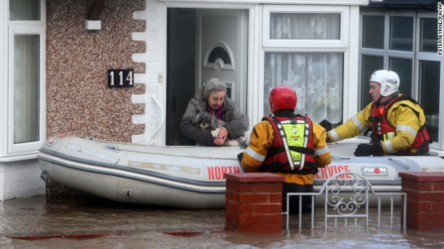 Members of the Royal National Lifeboat Institute rescue a woman and her dog from floodwaters in Rhyl, Wales, on December 5.