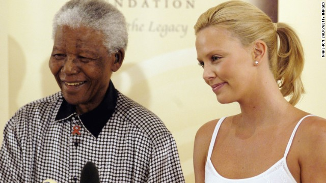 Actress Charlize Theron stands with Nelson Mandela in Johannesburg following her Academy Awards success in 2004.
