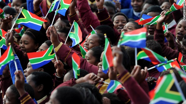 School kids from the Milton Mbekela school in South Africa wave flags.