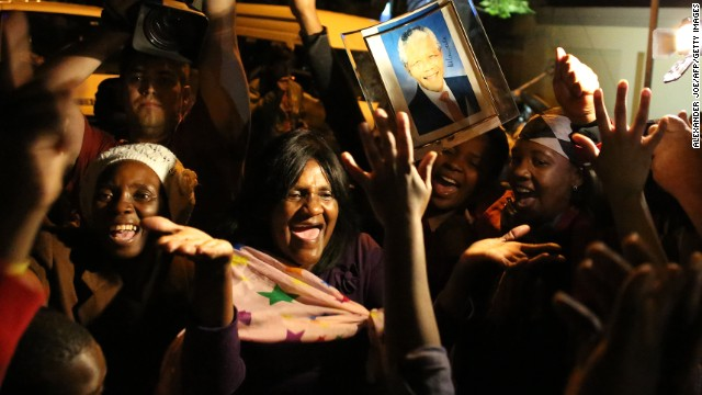 South Africans hold pictures of former South African president Nelson Mandela as they pay tribute following his death in Johannesburg on Friday, December 6.