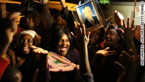 South Africans hold pictures of former South African president Nelson Mandela as they pay tribute following his death in Johannesburg on December 6, 2013