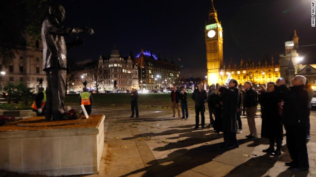 A small crowd gathers in front of a statue of Nelson Mandela at Parliament Square in London, on December 6.