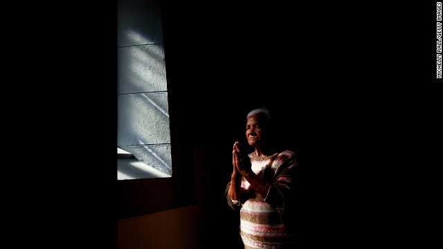 A woman prays at the Central Methodist Church as people remember Mandela on December 6 in CapeTown, South Africa.