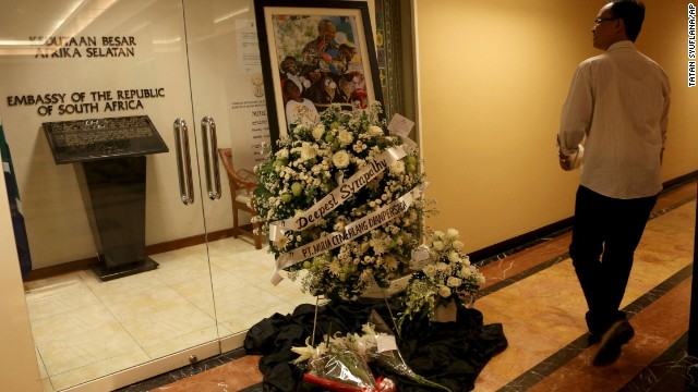A man looks at a wreath of flowers and a picture of Mandela displayed inside the embassy in Jakarta, Indonesia, on December 6.