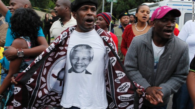 A man wearing a T-shirt with a portrait of Mandela leads a group of mourners as they sing and dance outside Mandela's Johannesburg home on December 6.