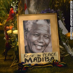 A framed image of former South African president Nelson Mandela as people pay tributes following his death, in Johannesburg on December 6, 2013.