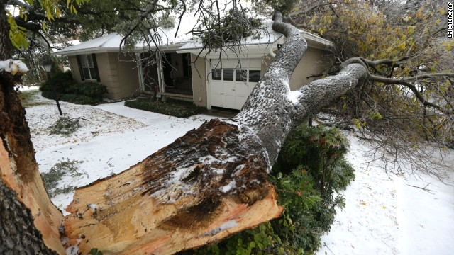A fallen tree rests on a house in Richardson, Texas, on December 6.