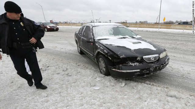 A police officer surveys a car damaged in an ice-related accident on a highway overpass in Richardson, Texas, on December 6.